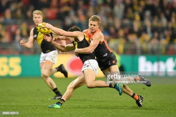 Jason Castagna of the Tigers is tackled by Adam Kennedy of the Giants during the round 17 AFL match between the Greater Western Sydney Giants and the...