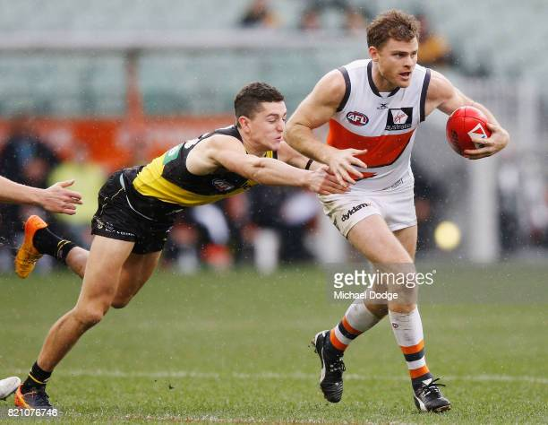 Jason Castagna of the Tigers tackles Heath Shaw of the Giants during the round 18 AFL match between the Richmond Tigers and the Greater Western...