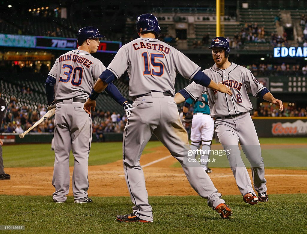 Jason Castro #15 and Trevor Crowe #8 of the Houston Astros are congratulated by Matt Dominguez #30 after scoring on a two-RBI double by Chris Carter in the ninth inning against the Seattle Mariners at Safeco Field on June 12, 2013 in Seattle, Washington.