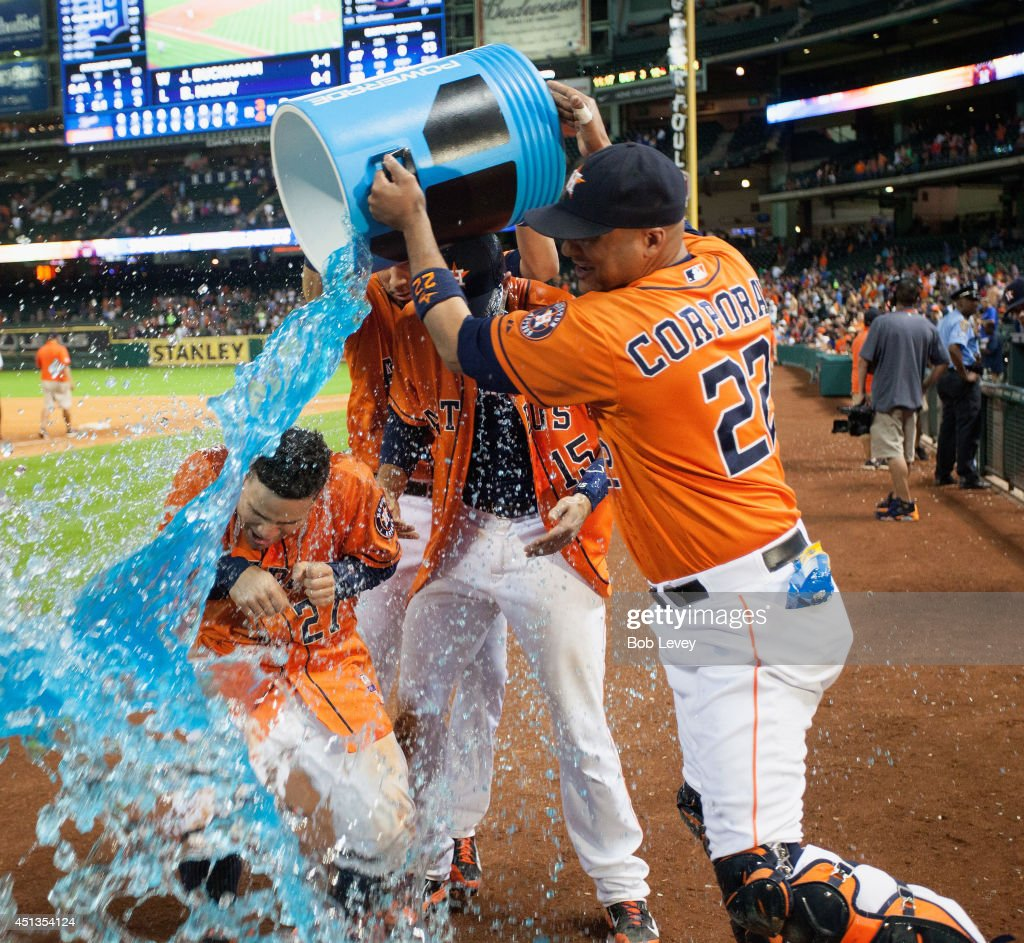 Jason Castro #15 of the Houston Astros and Jose Altuve #27 are doused with Poweraide by Carlos Corporan #22 after Castro hit a walk-off home run in the eleventh inning against the Detroit Tigers at Minute Maid Park on June 27, 2014 in Houston, Texas.