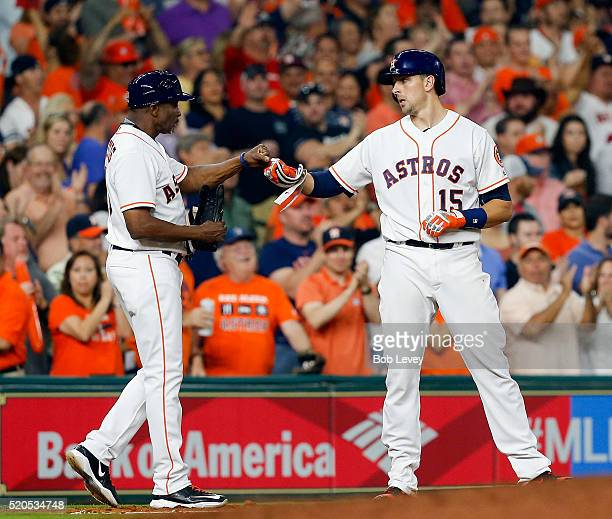 Jason Castro of the Houston Astros receives congratulation from third base coach Gary Pettis after hitting a triple in the fourth inning against the...