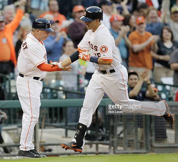 Jason Castro of the Houston Astros receives congratulations from third base coach Dave Trembley of the Astros after hitting a three run home run to...
