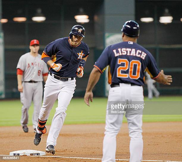 Jason Castro of the Houston Astros receives congratulations from third base coach Pat LIstach after hitting a home run in the first inning against...