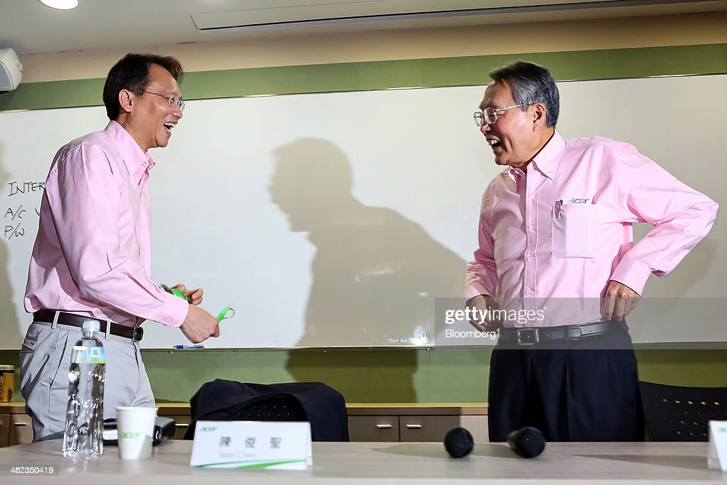 Jason Chen, chief executive officer of Acer Inc., left, and Stan Shih, co-founder and chairman, react as they arrive for a news conference at the company's headquarters in New Taipei City, Taiwan, on Monday, Jan. 13, 2014. Acers new chief executive officer plans to build on the Taiwanese personal computer makers existing hardware background to turn the company around from three years of losses. Photographer: Maurice Tsai/Bloomberg via Getty Images