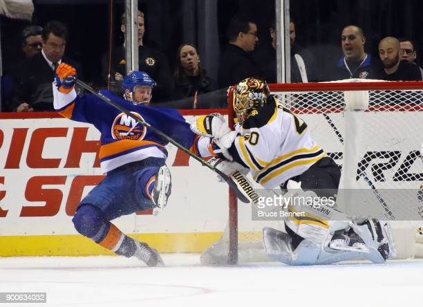 Jason Chimera of the New York Islanders gets tangled up with Tuukka Rask of the Boston Bruins during the first period at the Barclays Center on...