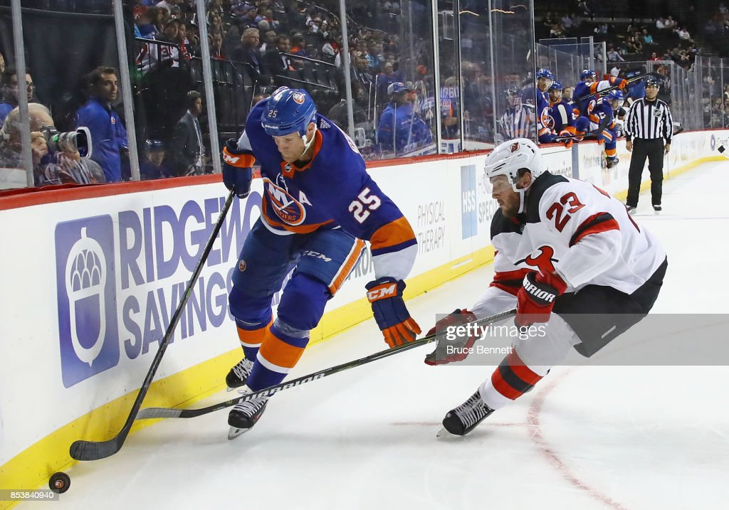 Jason Chimera #25 of the New York Islanders moves the puck around Stefan Noesen #23 of the New Jersey Devils during the second period during a preseason game at the Barclays Center on September 25, 2017 in the Brooklyn borough of New York City.