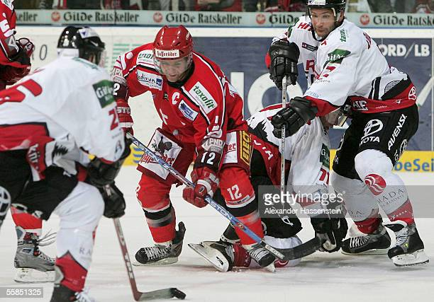 Jason Cipolla of Hanover in action with David McLlwain and Mirko Luedemann of Cologne during the DEL match between Hanover Scorpions and Cologne Haie...