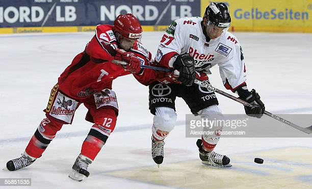 Jason Cipolla of Hanover in action with Nikolaus Mondt of Cologne during the DEL match between Hanover Scorpions and Cologne Haie at the TUI Arena on...