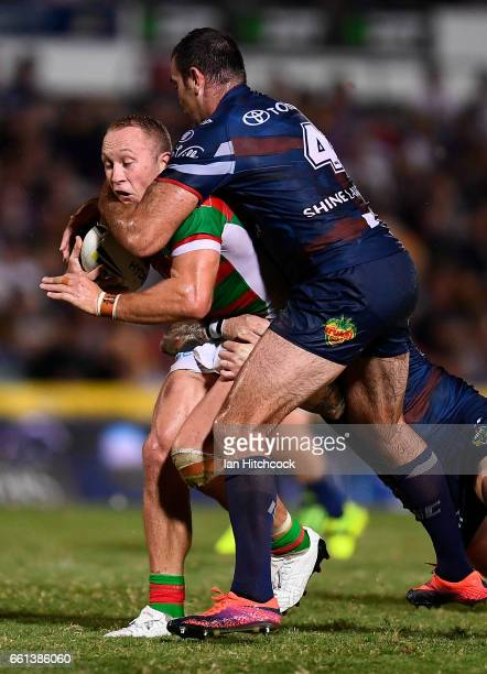 Jason Clark of the Rabbitohs is tackled by Kane Linnett of the Cowboys during the round five NRL match between the North Queensland Cowboys and the...