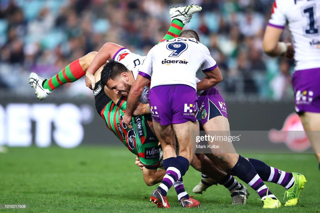 Jason Clark of the Rabbitohs is tackled by Kenny Bromwich, Nelson Asofa-Solomona and Cameron Smith of the Storm during the round 21 NRL match between the South Sydney Rabbitohs and the Melbourne Storm at ANZ Stadium on August 3, 2018 in Sydney, Australia.