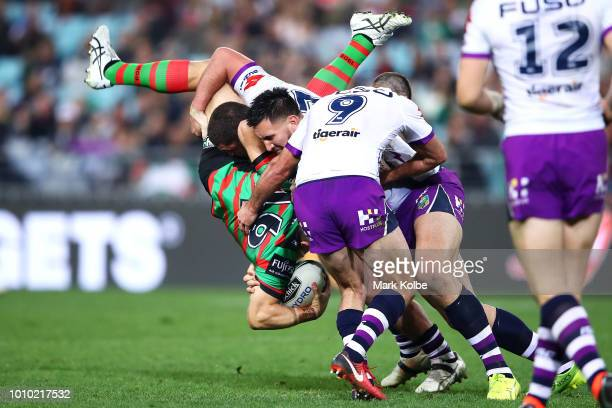 Jason Clark of the Rabbitohs is tackled by Kenny Bromwich Nelson AsofaSolomona and Cameron Smith of the Storm during the round 21 NRL match between...