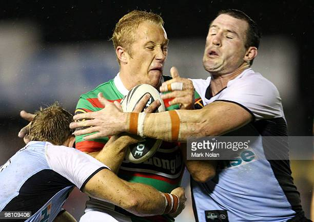 Jason Clark of the Rabbitohs is tackled by Paul Gallen of the Sharks during the round three NRL match between the Cronulla Sharks and the South...