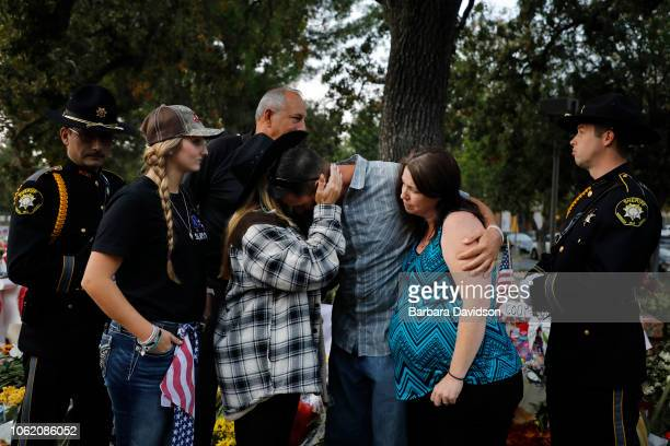 Jason Coffman, Father of slain victim Cody Coffman, gets a hug as his pregnant wife Shari, supports him at a vigil site for all the victims not far...