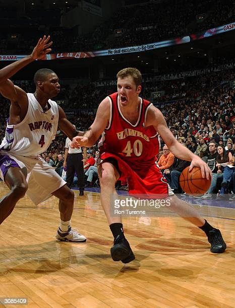 Jason Collier of the Atlanta Hawks drives against Chris Bosh of the Toronto Raptors March 15 2004 at the Air Canada Centre in Toronto Canada NOTE TO...