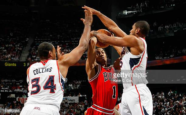 Jason Collins and Al Horford of the Atlanta Hawks defend against a a driving Derrick Rose of the Chicago Bulls in Game Four of the Eastern Conference...