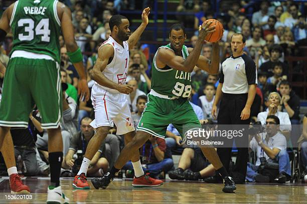 Jason Collins of the Boston Celtics protects the ball from Malik Hairston of the EA7 Emporio Armani Milano during the game between the Boston Celtics...