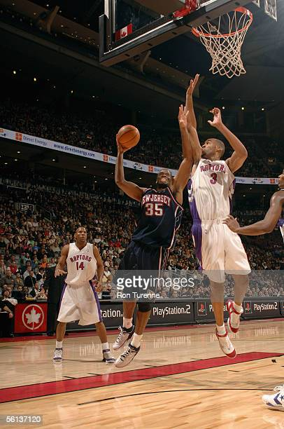 Jason Collins of the New Jersey Nets goes to the basket against Loren Woods of the Toronto Raptors during the game at Air Canada Centre on November 4...