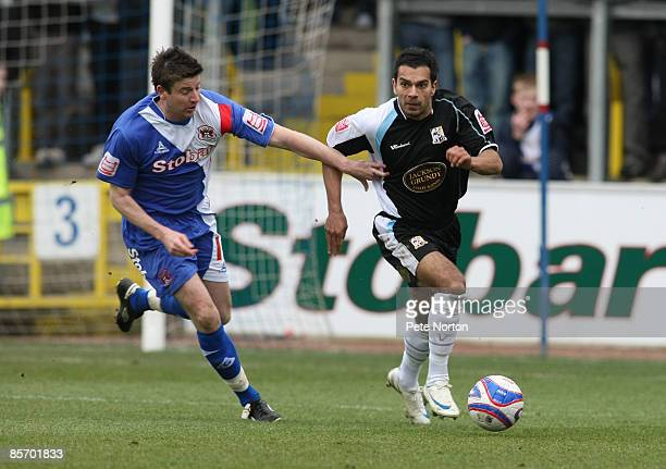 Jason Crowe of Northampton Town looks to move away from Michael Bridges of Carlisle United during the Coca Cola League One Match between Carlisle...