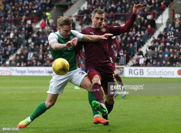 Jason Cummings of Hibernian and Aaron Hughes of Hearts battle for the ball during the Scottish Cup fifth round match between Heart of Midlothian and...