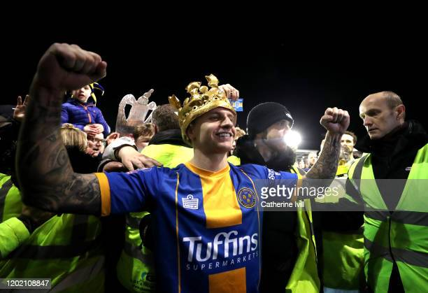Jason Cummings of Shrewsbury Town celebrates victory wearing a blowup crown during the FA Cup Fourth Round match between Shrewsbury Town and...