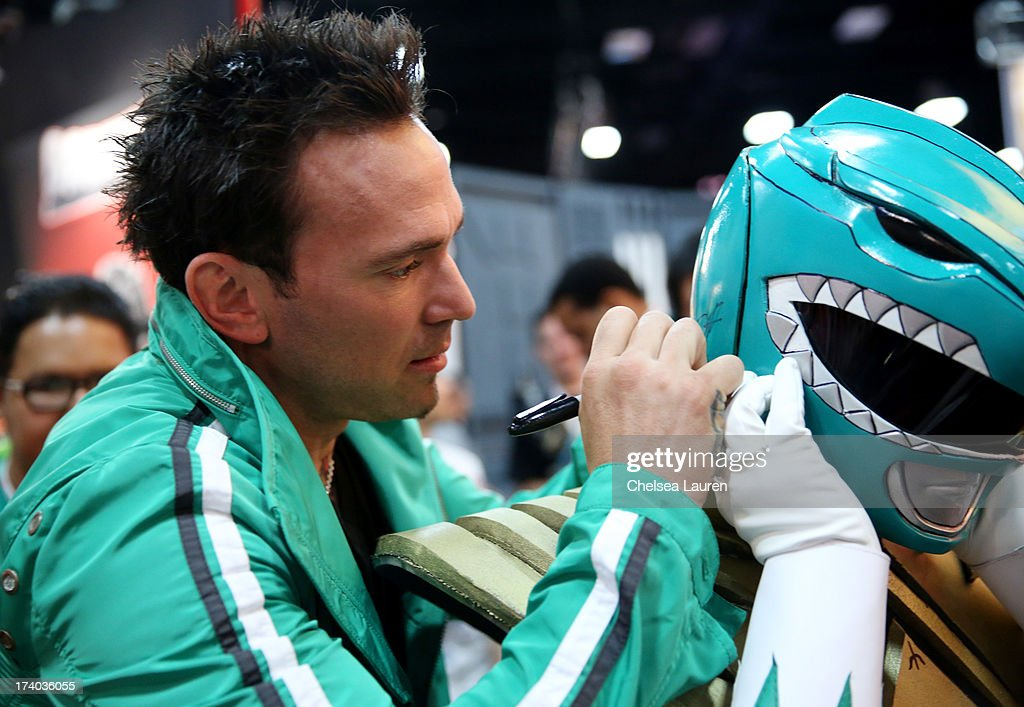 Jason David Frank, the Green Ranger from Mighty Morphin PowerRangers, signs the helmet of one of his fans dressed in costume during Comic-Con International 2013 at San Diego Convention Center on July 19, 2013 in San Diego, California.
