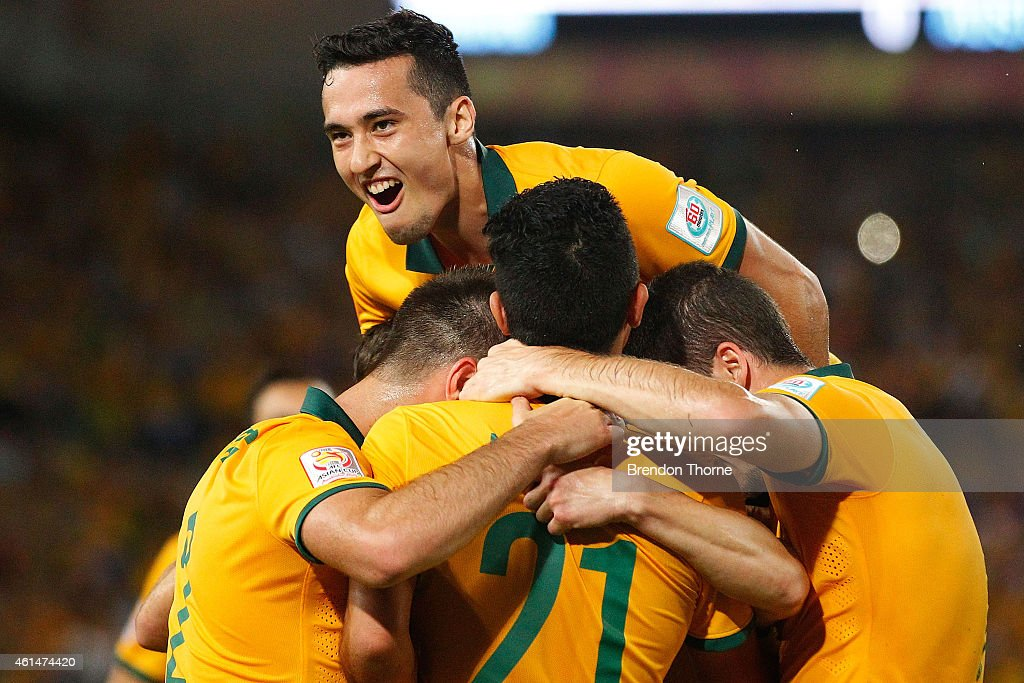 Jason Davidson of Australia jumps on his team-mates in celebration after Robbie Kruse of Australia scored a goal during the 2015 Asian Cup match between Oman and Australia at ANZ Stadium on January 13, 2015 in Sydney, Australia.