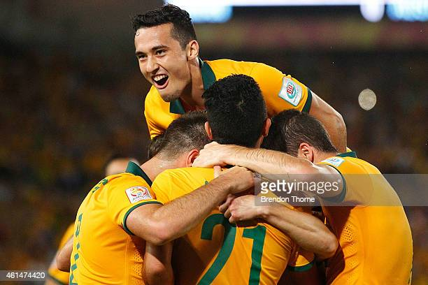 Jason Davidson of Australia jumps on his teammates in celebration after Robbie Kruse of Australia scored a goal during the 2015 Asian Cup match...