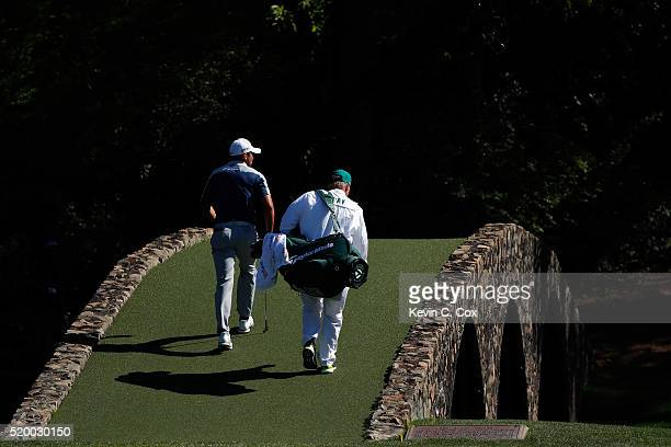 Jason Day of Australia and caddie Colin Swatton walk across the Hogan bridge to the 12th green during the third round of the 2016 Masters Tournament...