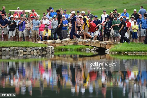 Jason Day of Australia and Emiliano Grillo of Argentina walk with their caddies over the bridge on the fourth hole during the final round of the 2016...