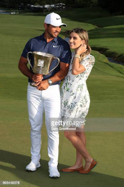 Jason Day of Australia and his wife Ellie pose with the trophy on the 18th green after winning the 2018 Wells Fargo Championship at Quail Hollow Club...