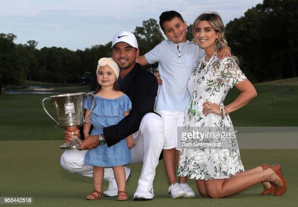 Jason Day of Australia and his wife Ellie pose with their children, Dash and Lucy, on the 18th green after winning the 2018 Wells Fargo Championship...