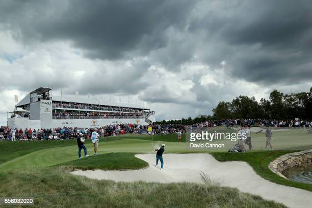 Jason Day of Australia and the International team plays his third shot on the ninth hole in his match with Louis Oosthuizen against Patrick Reed and...