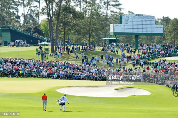 Jason Day of Australia approaches the second green with caddie Colin Swatton during the third round of the 2017 Masters Tournament at Augusta...