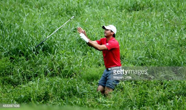 Jason Day of Australia catches a golf club before hitting a shot out of the deep grass on the second hole during the third round of the 96th PGA...