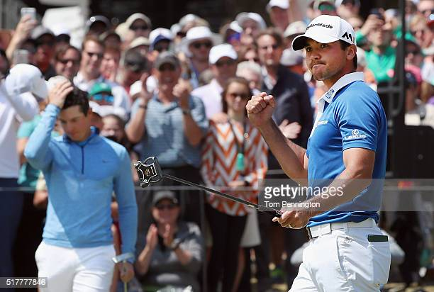 Jason Day of Australia celebrates his parsaving putt on the 18th green to defeat Rory McIlroy 1up during their semifinal match at the World Golf...
