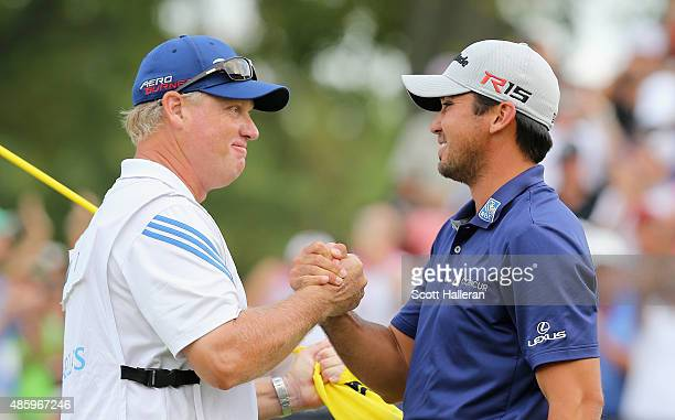 Jason Day of Australia celebrates on the 18th green with his caddie Colin Swatton after his sixstroke victory at The Barclays at Plainfield Country...
