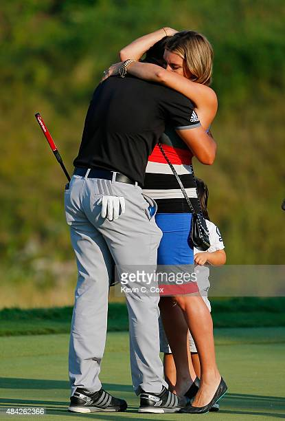 Jason Day of Australia celebrates on the 18th green with his wife Ellie and son Dash after winning the 2015 PGA Championship with a score of 20under...