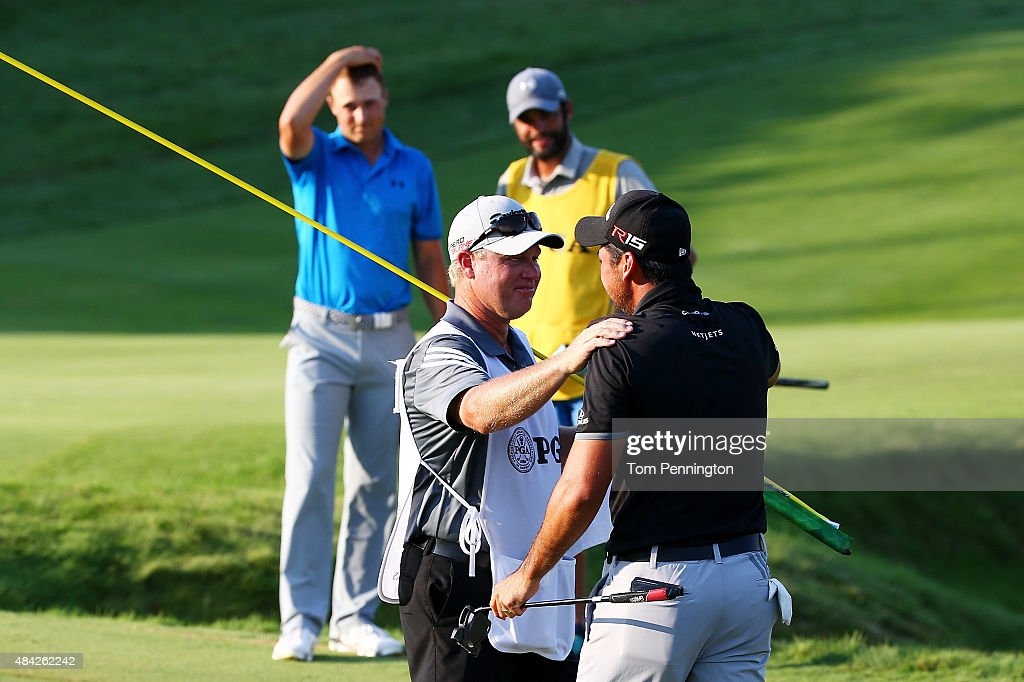 Jason Day of Australia celebrates with his caddie Colin Swatton on the 18th green after winning the 2015 PGA Championship with a score of 20-under par as Jordan Spieth of the United States and caddie Mike Greller look on at Whistling Straits on August 16, 2015 in Sheboygan, Wisconsin.