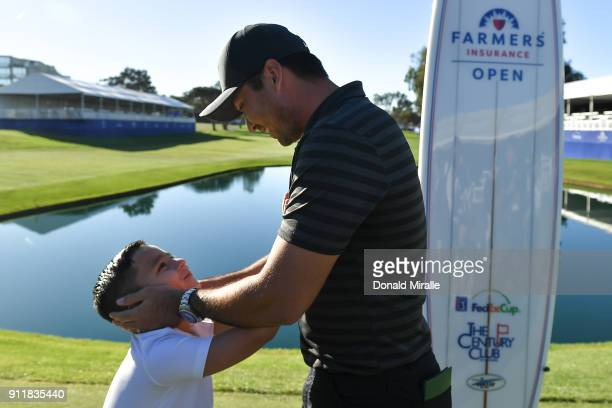 Jason Day of Australia celebrates with his son Dash after winning the Farmers Insurance Open on the sixth playoff at Torrey Pines South on January 29...