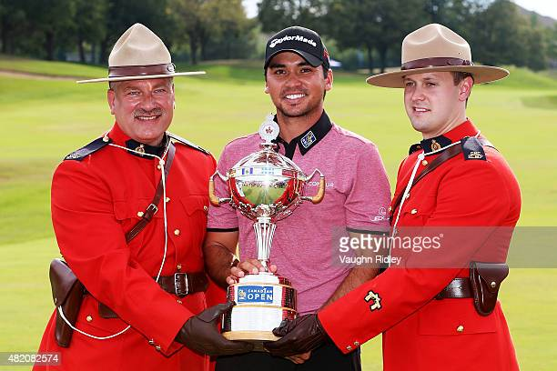 Jason Day of Australia celebrates with Royal Canadian Mounted Police the winner's trophy after the final round of the RBC Canadian Open at Glen Abbey...