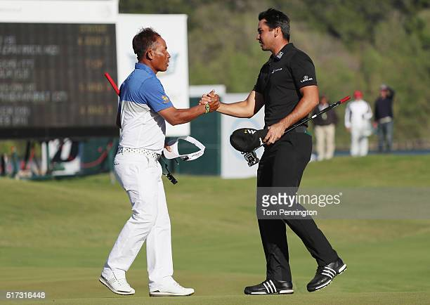 Jason Day of Australia greets Thongchai Jaidee of Thailand on the 15th green after Day won their match 5&3 during the second round of the World Golf...