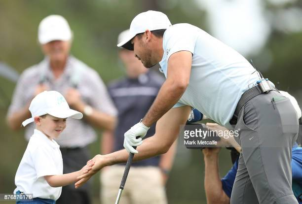 Jason Day of Australia high fives with 5 year old golfer Isaac Riches during a practice round ahead of the 2017 Australian Open at The Australian...