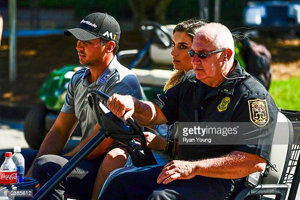 Jason Day of Australia is driven off the course with his wife Ellie after withdrawing due to back problems during the second round of the TOUR...