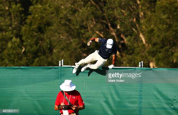 Jason Day of Australia jumps a fence after playing into the rough during day one of the 2013 Australian Open at Royal Sydney Golf Club on November 28...
