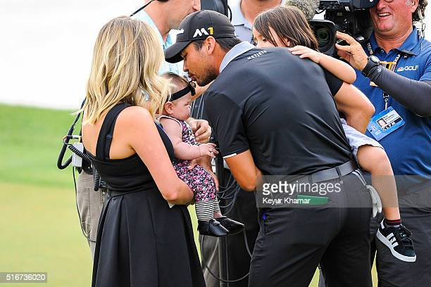 Jason Day of Australia kisses his daughter Lucy with son Dash and wife Ellie following his one stroke victory on the 18th hole green during the final...