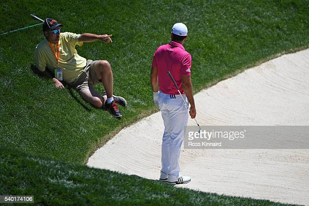 Jason Day of Australia looks on as Christopher Crawfords' caddie waits for a stretcher after injuring himself during a practice round prior to the US...
