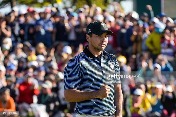 Jason Day of Australia on the International Team celebrates his 1up victory with Adam Scott of Australia after a birdie putt on the 18th hole green...