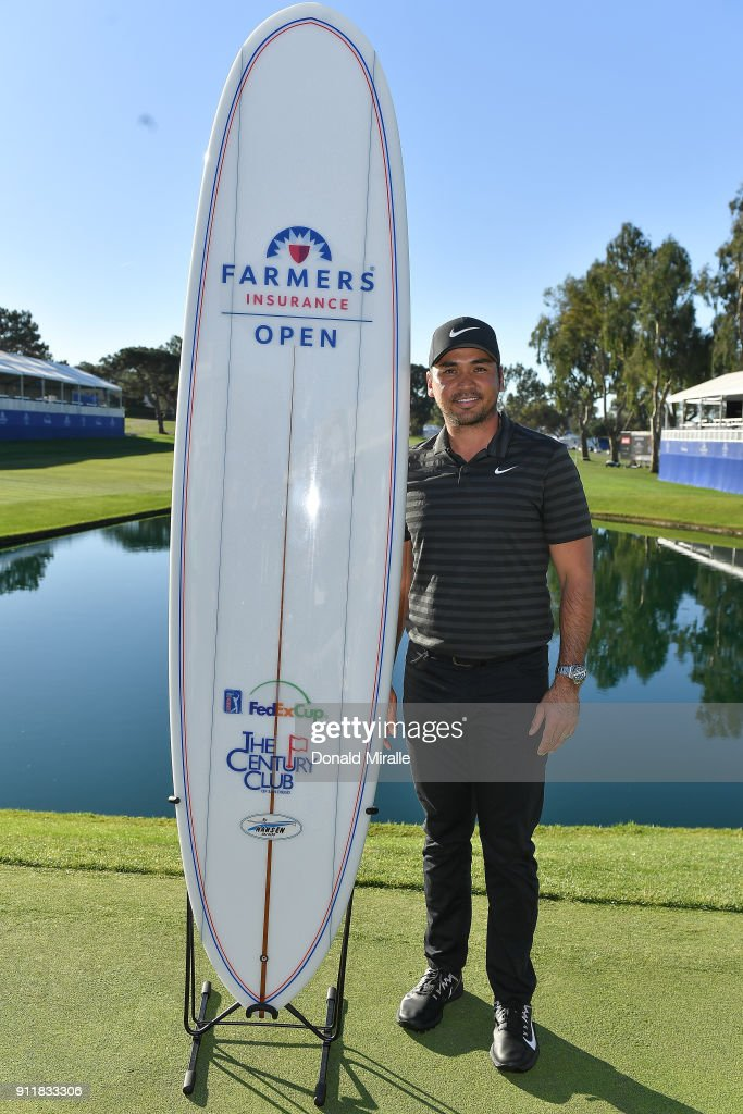Jason Day of Australia poses with the winner's surfboard after the sixth playoff on the 18th hole to win the Farmers Insurance Open at Torrey Pines South on January 29, 2018 in San Diego, California.