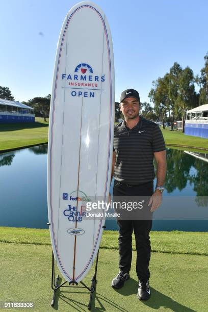 Jason Day of Australia poses with the winner's surfboard after the sixth playoff on the 18th hole to win the Farmers Insurance Open at Torrey Pines...