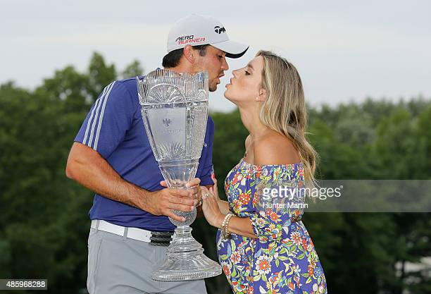 Jason Day of Australia poses with the winner's trophy on the 18th green alongside his wife Ellie after his sixstroke victory at The Barclays at...